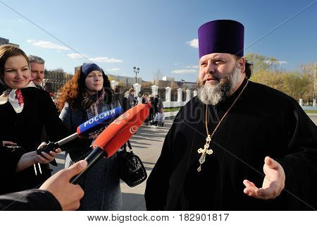 Orel Russia - April 20 2017: Orthodox bell-ringing festival. Alexander Prishchepa Bogoyavlenskaya church abbot in black robe giving interviews to local TV