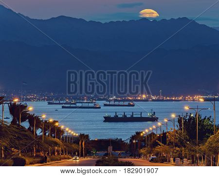 Rising of super-moon above Jordanian mountains, view from the longest street in Eilat - famous resort in Israel and Middle East