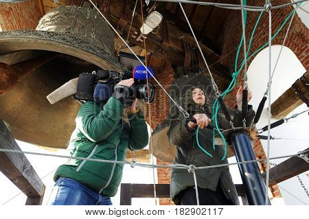 Orel Russia - April 20 2017: Orthodox bell-ringing festival. Woman in black ringing church bells and camera man shooting news
