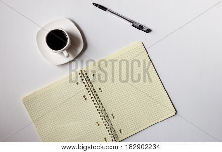 There is a note-book and a pen on the table