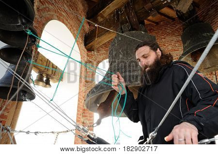 Orel Russia - April 20 2017: Orthodox bell-ringing festival. Bearded man in black ringing bells in belfry horizontal