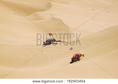 Couple of ATV riders kicking off sand in vast california desert
