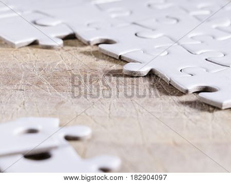 close up of a white jigsaw over a wooden table. business. strategy.