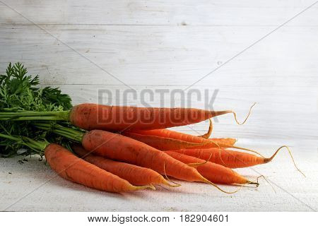 Carrot bunch on white painted rustic wood with copy space fresh organic vegetables with vitamins for health