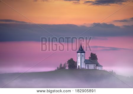 Idyllic landscape photo of Church Of St. Primoz - Slovenia at colorful sunset.
