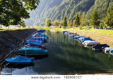 Sunny foggy morning in the Swiss Alps. Mountain lake Klontalersee on background of majestic mountains. Camping on the shore of the montain lake Klontalersee. Boats on the dock. Glarus canton. Switzerland.