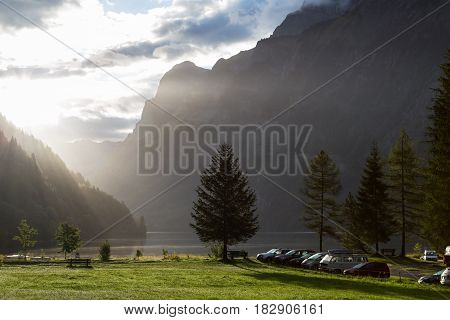 Foggy morning in the Swiss Alps. Mountain lake Klontalersee on background of majestic mountains. Camping on the shore of the lake. Glarus canton. Switzerland.