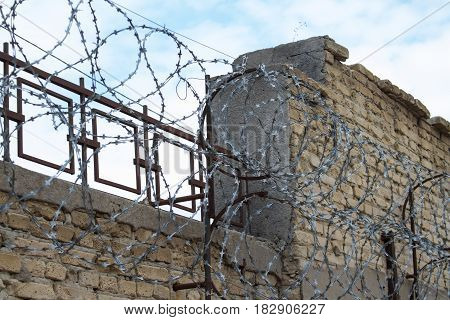 Barbed wire fence against the blue sky