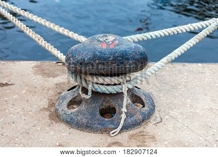 Mooring metal bollard with a fixed rope at the pier