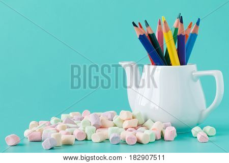 Colorful Stationery In White Kettle On Aquamarine Background