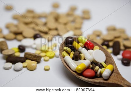 Tablets And Capsules On Wooden Spoon