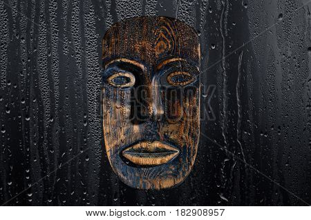 Brown wood mask on a black background, through a drop of water