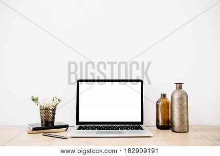 Blogger or freelancer workspace with front view of laptop with blank screen at white background. Minimalistic decorated home office desk.