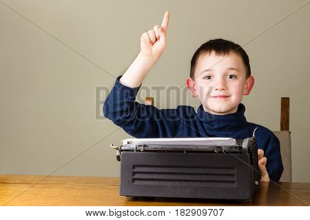 Cute little happy boy raising finger behind an old vintage black typewriter at home