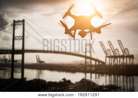 Silhouette of Unmanned Aircraft System (UAV) Quadcopter Drone In The Air Over Shipping Port.