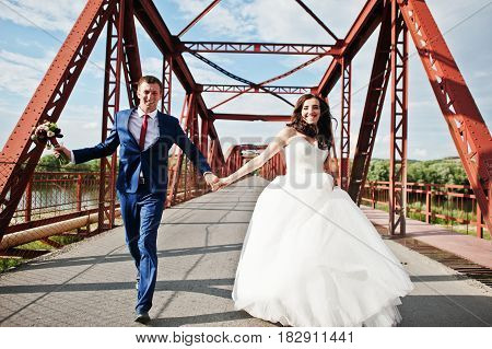 Wedding Couple In Love Stay At Red Railway Bridge.