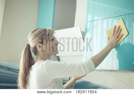 Young woman in the Kitchen doing Housework cleaning cupboards.