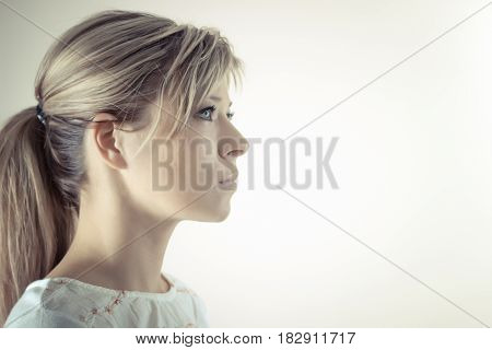 Profile of a beautiful serious blond woman.