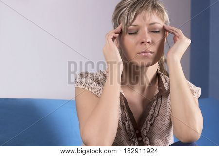 Young woman sitting on a couch holding her head having a strong headache.