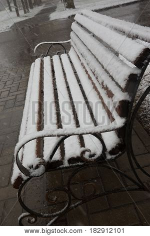 Closeup view of a bench smoothly covered with fresh snow after weather phenomena - snowfall in late April near Moscow
