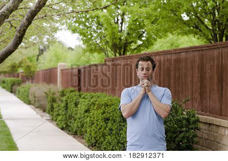 Man outside stopping to pray while on a walk.