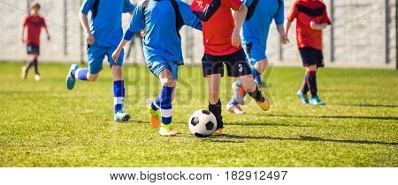 Young Boys Soccer Players Kicking Football on the Sports Field. Running Footballers in Blue and Red Jersey Shirts. Youth Soccer Horizontal Background