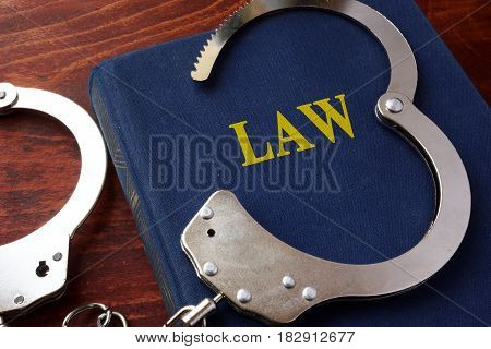Cuffs and book with the title Law.