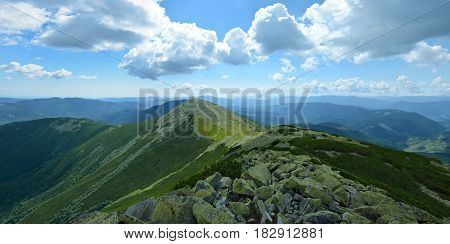 Panoramic view of the mountain ridge in Carpathians Ukraine. Big stones with green moss on the foreground.