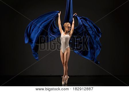 Young pretty female gymnast in white lingerie exercising on blue aerial silks studio shot