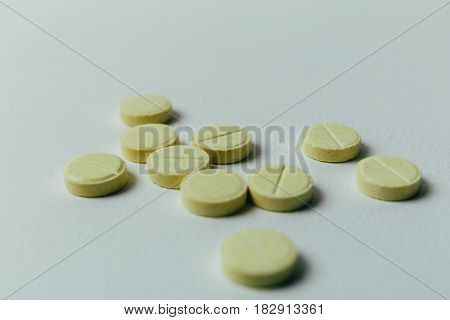 Yellow pills on a light background, close up image with copy space, toned