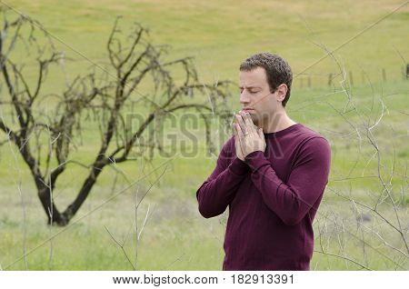 Man praying outside in an empty field with a bare tree in the background.