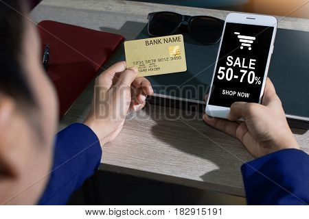 Young woman holding credit card and using smartphone.
