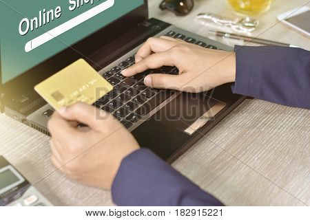 Hands holding credit card and using laptop. Online shopping concept.