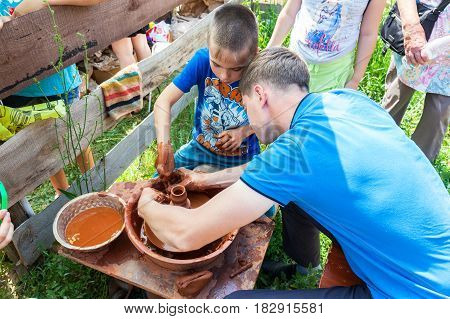 Samara Russia - june 18 2016: Teacher helps his student to work with red clay. Work on the potter's wheel at the outdoors