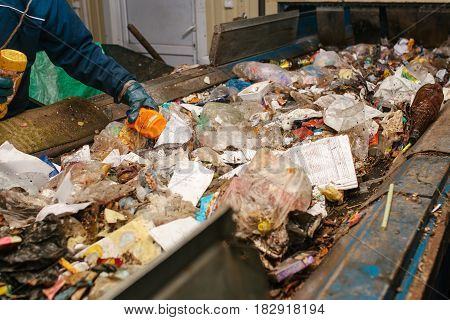 The worker sorts the waste received by a modern plant for sorting and recycling waste. Waste processing plant. Technological process. Recycling and storage of waste for further disposal.