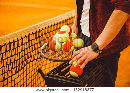 Hand Man Holding A Tennis Racket And A Lot Of Goals. Basket For Tennis Balls,