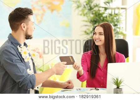 Adventure concept. Young man visiting travel agency