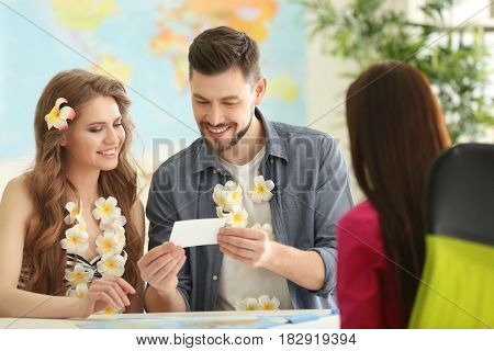 Adventure concept. Young couple watching photos visiting travel agency