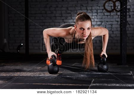 Young beautiful sporty woman in the black sportwear doing a pushups with kettlebell against brick wall at the crossfit gym. Close-up horizontal photo. T-shirt, leggings and sportive shoes. Healthy lifestyle.