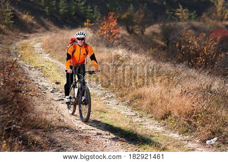 Cyclist in the orange jacket riding a bike on countryside road at the sunrise. Sportsman in the sportwear, white helmet, sunglasses and with red backpack. Summer time. Travel in the countryside. Healthy lifestyle.