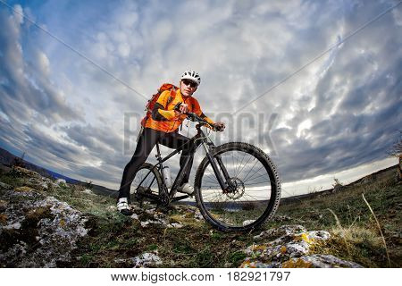 Bottom view photo of cyclist in orange jacket standing with his bike on the rock against blue sky with clouds. Sportsman in the helmet, sunglasses and with red backpack. Extreme travel in the countryside. Summer season. Healthy lifestyle. Fisheye.