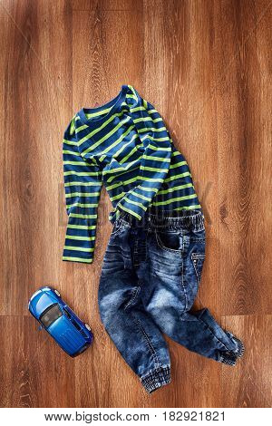 Children's jacket and jeans with blue toy car on a wooden background. Green jacket in stripes and blue jeans. Concept of the children's fashion industry. Clothes for boys.
