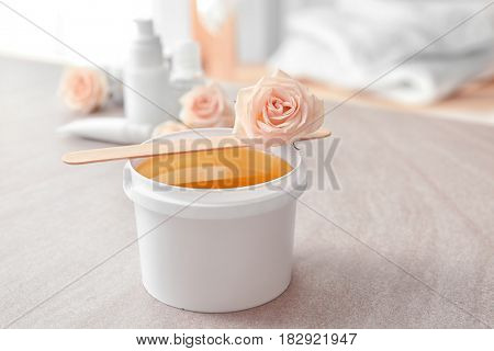 Plastic bucket with sugaring paste, wooden stick and flower on table