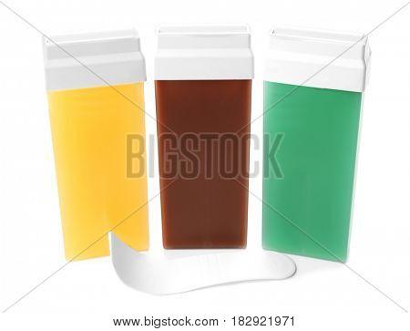 Liposoluble wax cartridges and spatula on white background
