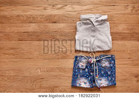 Children's jeans and jacket on wooden background. White jacket with hood and blue jeans in flowers. Clothes for little girl. Casual and modern chidren's style. Concept of the children's fashion industry.