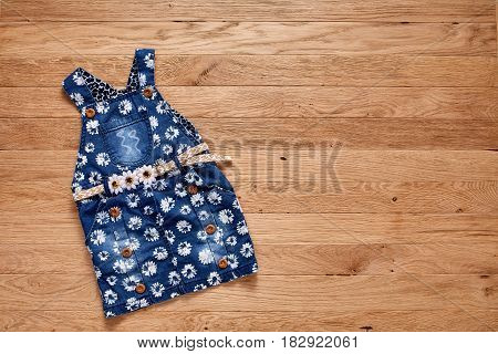 Cute denim dress on wooden background. Denim dress in flowers and with cute belt. Clothes for little girl. Casual and modern chidren's style. Concept of the children's fashion industry.