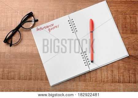 Text INSURANCE QUOTES written in notebook on wooden background
