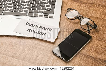 Card with text INSURANCE QUOTES, laptop and smartphone on wooden background