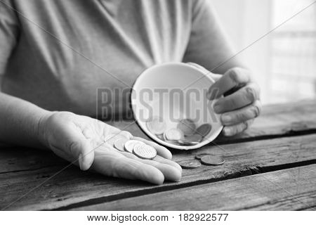 Senior woman sitting at table with bowl and coins, closeup. Poverty concept