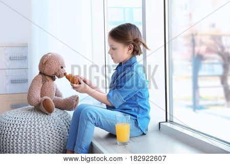 Cute little girl feeding toy with croissant while sitting on window sill at home